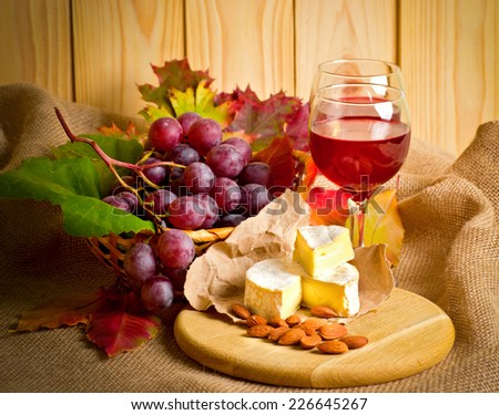 Red wine with cheese, almonds and grapes on sackcloth on a background of a wooden wall and autumn leaves