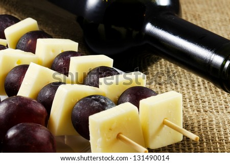 Red wine with cheese and red grapes close up image - stock photo