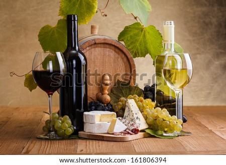 Red wine with cheese and white grape snack in front of small barrel - stock photo