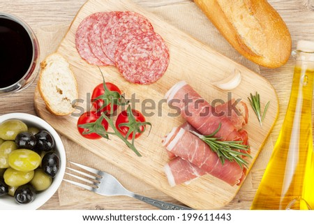 Red wine with cheese, prosciutto, bread, vegetables and spices on wooden table