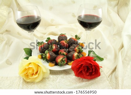 Red wine with chocolate covered strawberries, chocolate covered apricots and roses. - stock photo