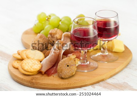 red wine with dry fruits, cookies and cheese
