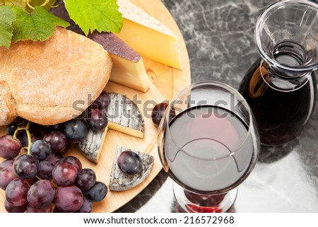 Red wine with wine grapes cheese plate and bread - stock photo