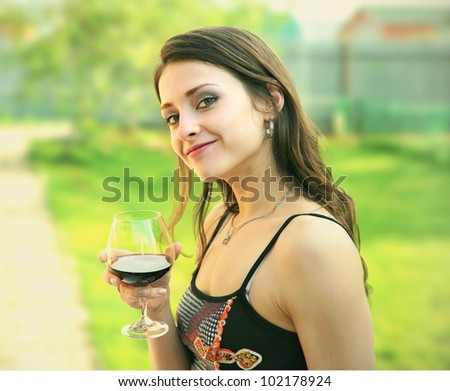 Red wine. Woman drinking red wine with happy smiling outdoor on nature green background - stock photo