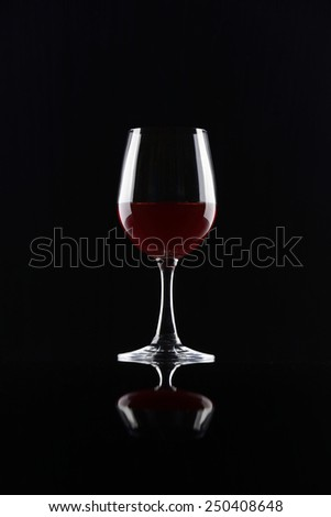 Red wineglass isolated on black background - stock photo