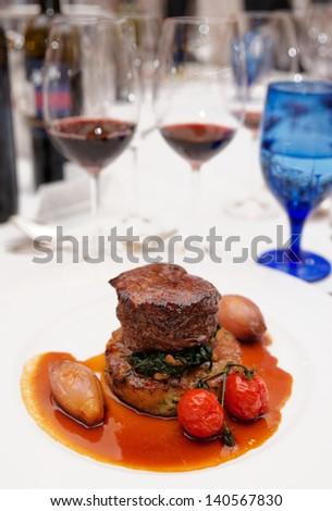 Red wines and tenderloin steak on restaurant table - stock photo
