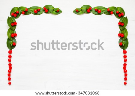 Red winter berries and green ivy leaves on snow. Christmas background.