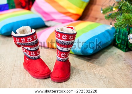 Red winter fur boots next to decorated Christmas tree with pillows on the floor - stock photo