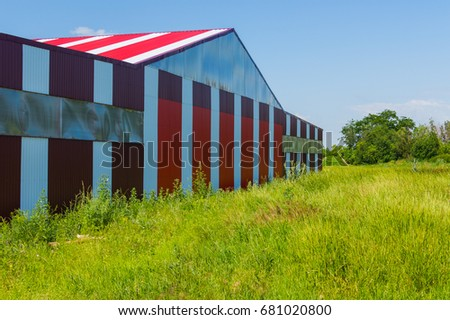 Red with white stripes building on the airfield field in the countryside
