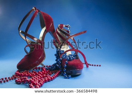 Red woman high heels with pearls over blue backgrounds - stock photo