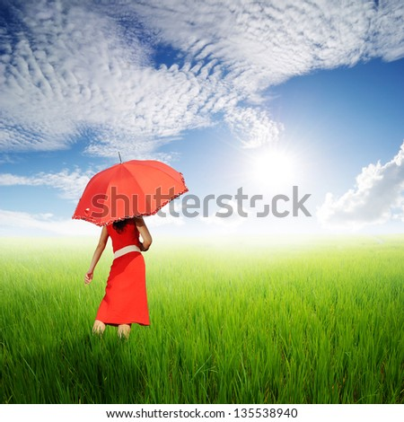 Red Woman holding umbrella in green rice fields in sun sky