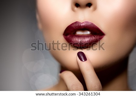 Red woman lips close up. Beautiful model girl with lipstick, manicure with nail polish Products Treatment - stock photo