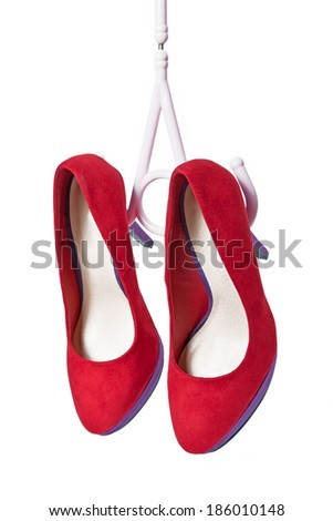 Red womens shoes on hairpins hang on the coat hanger on a white background - stock photo
