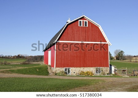 Red wooden barn on a Wisconsin farm with green grass and blue sky in the background