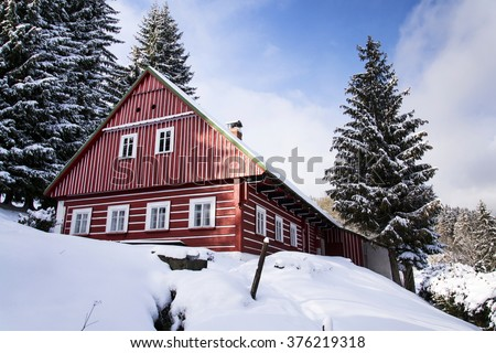 Red wooden cabin in a frosty snowy country in sunny winter day - stock photo