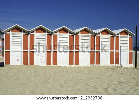 Red wooden cabins on the beach. - stock photo