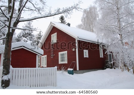 Red wooden Finnish house in winter covered with snow - stock photo