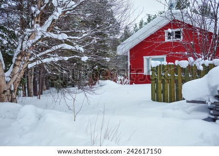 Red wooden Finnish house in winter forest covered with snow - stock photo