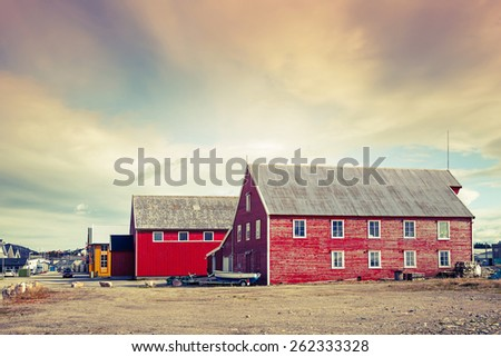 Red wooden fishing barns on the coast in Rorvik town, Norway. Vintage toned photo with retro style instagram filter - stock photo