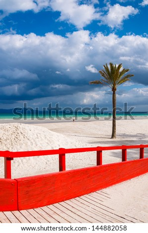 Red wooden footbridge walkway beach sea white clouds blue sky palm tree, Alcudia, Majorca island, Spain