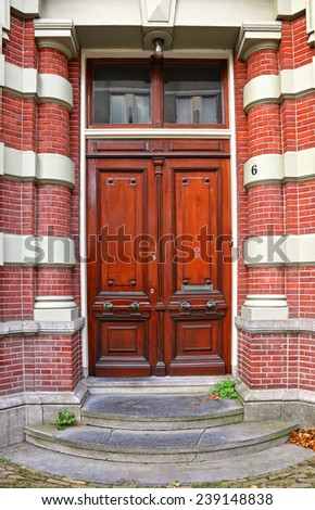 Red wooden glass door of an old stone classical building, Europe. Architectural theme.  - stock photo