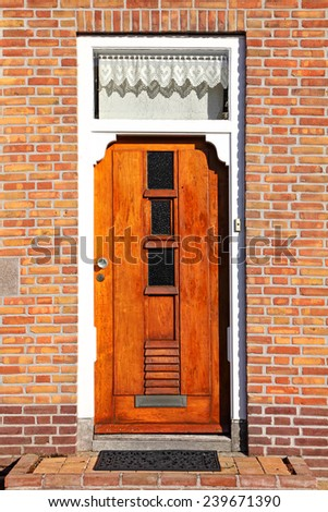 Red wooden glass door of an old stone classical building. Europe. Architectural theme - stock photo