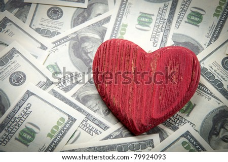 Red wooden heart on dollar bills - stock photo