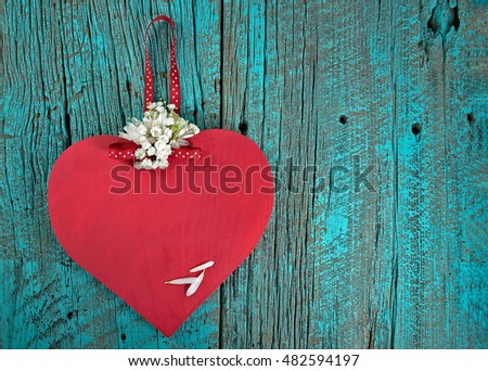red wooden heart on turquoise painted barn wood with daisies and baby's breath