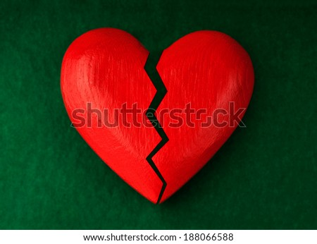 Red wooden heart with crack.