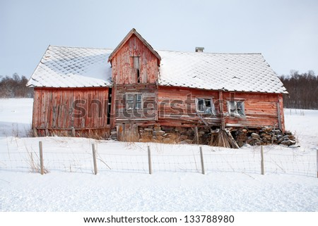 Red wooden house in ruins on a snowy hill . Troms county, Norway .