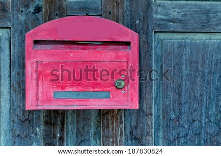 red wooden mail box on grunge wooden wall. - stock photo