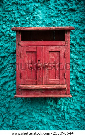 Red wooden mailbox on blue texture wall  - stock photo