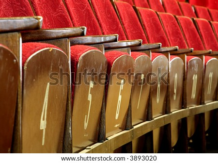 red wooden seats in theater, numbers on seats