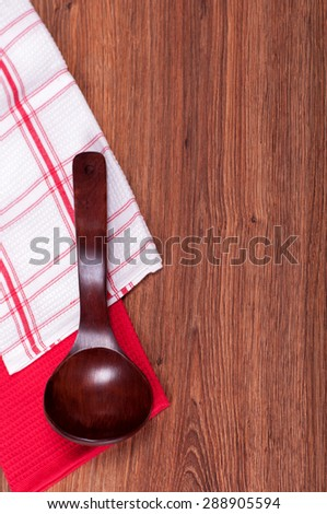 red wooden spoon white and red towel and wooden background - stock photo