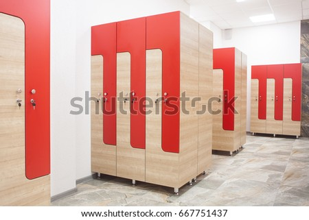 Red wooden sports wardrobe in the gym for clothes and a wooden bench