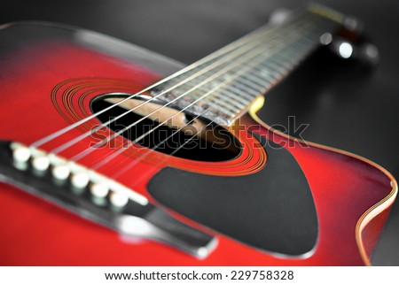 Red wooden top acoustic guitar  - stock photo
