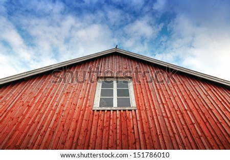 Red wooden wall with window above blue cloudy sky. Typically fishing house in Norway  - stock photo