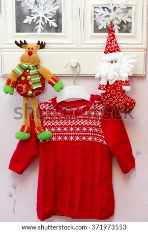 Red wool dress for baby girl and two christmas toys - santa, deer - hanging on picture frame