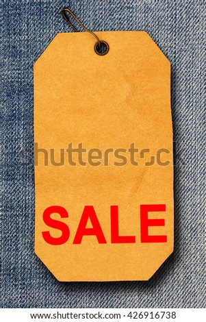 Red Word SALE on rumpled brown paper label  with brown pin on blue denim jeans background, Close up    - stock photo