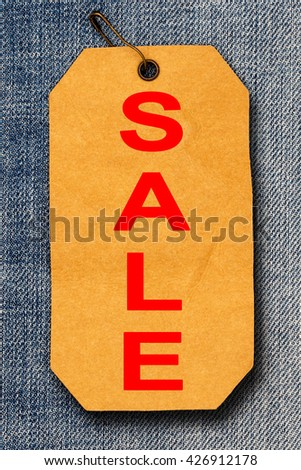 REd Word SALE on rumpled brown paper label  with brown pin on destroyed torn blue jeans background  , Close up - stock photo