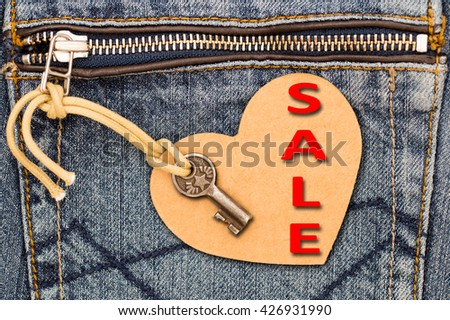 Red Word SALE, Vintage key, paper label in the shape of a heart on a jeans pocket with Zip, close up  - stock photo