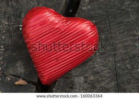 Red wrapped heart on wooden background - stock photo