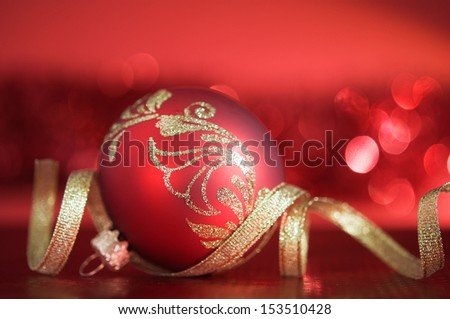 Red xmas ball with golden ribbon on red blurred background - stock photo