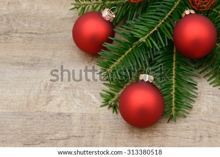 Red xmas bauble and fir branch lying on wood - stock photo