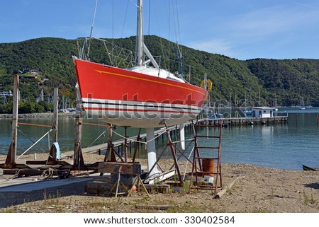 Red Yacht being repaired at a Shipyard in Waikawa Marina, Picton, New Zealand. - stock photo
