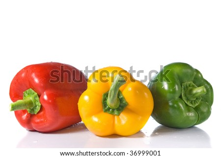 red, yellow and green pepper with water drops isolated on white
