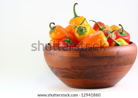 Red, yellow and orange mini peppers in a wooden bowl with copy space to the left.