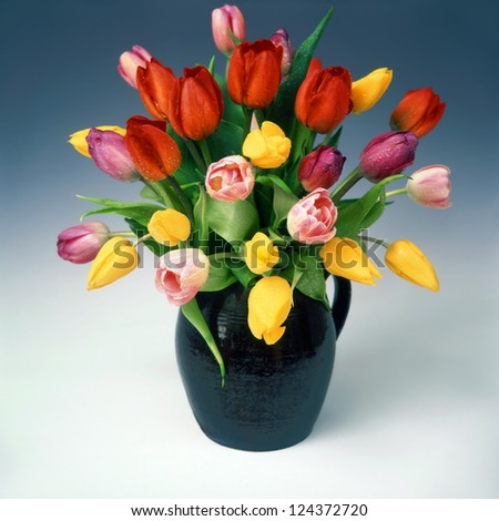 Red, yellow and pink tulips in old jug. - stock photo