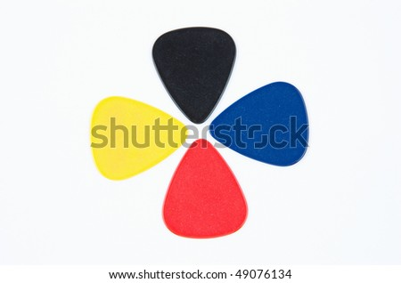 Red, yellow, black and blue guitar picks arranged in a petal pattern - stock photo