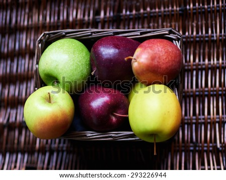 Red, yellow, green apples are in a small wicker basket. Fresh fruit torn from the garden - stock photo